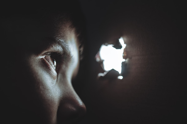 Barn tittar ut genom hål utsatt för trauma PTSD - legitimerad psykolog Kristoffer Pettersson Stockholm